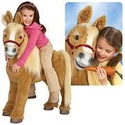 Flicka i femårsåldern rider på en leksakspony som är ungefär lika hög som hon.