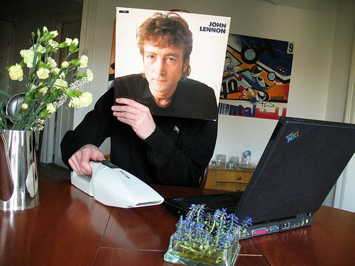 Man håller upp omslag med John Lennon framför sitt ansikte, och det är svårt att se var omslaget slutar och verkligheten börjar