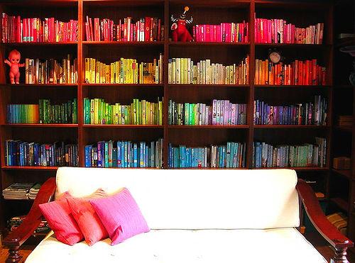 Bokhylla med böckerna sorterade i färgordning.